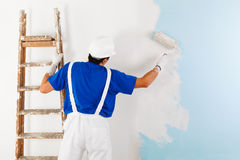 Painter painting a wall with paint roller. Back view of  painter in white dungarees, helmet and gloves painting a wall with paint roller and wooden vintage Royalty Free Stock Image