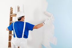 Painter painting a wall with paint roller stock photography