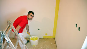 Painter Painting a Wall with a Paint Roller Stock Images
