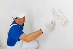 Painter painting a wall with paint roller Stock Image