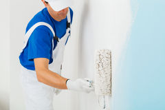 Painter painting a wall with paint roller. Side view of  painter with cap and gloves painting a wall with paint roller, selective focus on paint roller Stock Photo