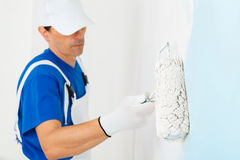 Painter painting a wall with paint roller. Side view of  painter with cap and gloves painting a wall with paint roller, selective focus on paint roller Royalty Free Stock Photos