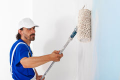 Painter painting a wall with paint roller. Side view of painter in white dungarees and cap painting a wall with paint roller; copy space Stock Photos
