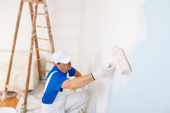 Painter painting a wall with paint roller. Side view of  painter in white dungarees, cap and gloves painting a wall with paint roller and wooden vintage ladder Royalty Free Stock Photo