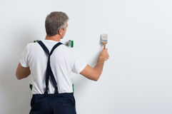 Painter Painting Wall. Painter On Stepladder Painting Wall With Brush Royalty Free Stock Images