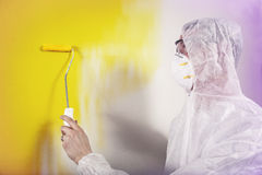 Painter painting wall wearing overalls Stock Image