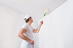 Painter Painting On Wall. Young Painter In White Uniform Painting With Paint Roller On Wall Stock Photography