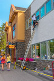 Painter painting window trim in Banff Business District Stock Photo