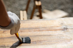 Painter painting wooden surface, protecting wood Royalty Free Stock Photography
