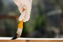 Painter painting wooden surface, protecting wood Stock Photography