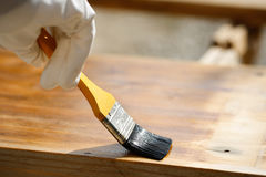 Painter painting wooden surface, protecting wood Royalty Free Stock Photos