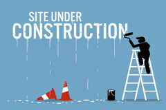 Painter painting the word site under construction on a wall. Royalty Free Stock Photos