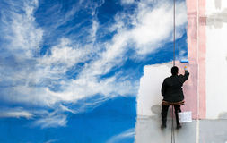 Painter paints bright blue sky on the wall Stock Photos