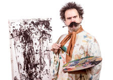 Painter paints on canvas. Serious painter paints on canvas isolated on white background stock photo