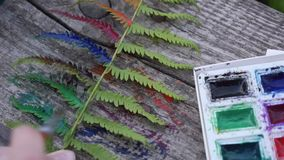 Colored ferns - paints. The painter paints green ferns in color stock footage