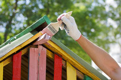 The painter paints the roof. Of toy house Stock Photography