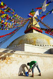 A painter paints a surface of Boudhanath stupa stock images