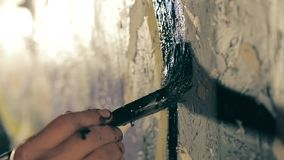 The painter paints the wall in black color. Closeup shot of the painter`s hand paints the wall in black color stock footage