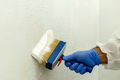 Painter paints the wall with the tint of white. Royalty Free Stock Photo
