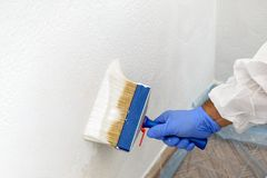 Painter paints the wall with the tint of white. Royalty Free Stock Photography