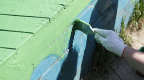 The painter paints the wooden structure. In the green color Royalty Free Stock Photography