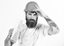 Painter, plasterer, repairman, foreman in helmet or hard hat holds putty knife, plastering tool. Brutal repairman. Concept. Bearded repairman with tired face royalty free stock photography