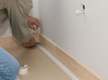 Painter preparing to paint. Builder masking floor in preparation for painting skirting boards DIY Stock Images