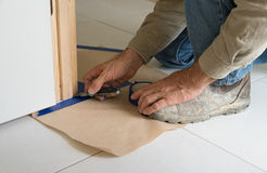 Painter preparing to paint. Builder masking floor in preparation for painting timber finishes DIY Royalty Free Stock Photo