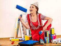 Painter repair home woman holding paint roller for wallpaper. Girl in newspaper cap renovation apartment . Successfully chosen profession Royalty Free Stock Photos