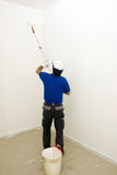 Painter with a roll. House painter at work in a house painting a wall Royalty Free Stock Images