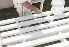 Painter Rolling White Paint Onto Top of Patio Cover Royalty Free Stock Photography