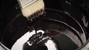 Painter's brush dipped in a bowl of thick bitumen stock footage