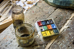 Painter's Equipment. Painter's Jars And Colour Palette on old brown table Stock Photos