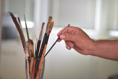Painter's hand taking a brush Royalty Free Stock Image