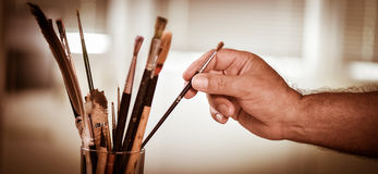 Painter's hand taking a brush Royalty Free Stock Photos