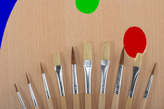 A Painter's Palette with Many Brushes. A painter's palette with many different sized brushes and different color spots Stock Images
