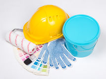 Painter's tools - brushes, work gloves, helmet and bucket of blu Stock Photo