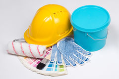 Painter's tools - brushes, work gloves, helmet and bucket of pai Stock Photos