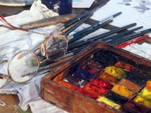 The painter's workstation. The workstation of a street painter in Venice - paints, brushes and glasses Stock Photo