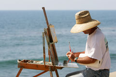 Painter at the Seaside. Sitting at Easel working a Painting Royalty Free Illustration