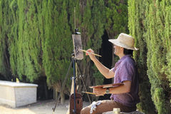 Painter is sitting in Barcelona ciudadela park among green plants Royalty Free Stock Images
