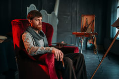 Painter sitting on chair, art studio on background stock photography