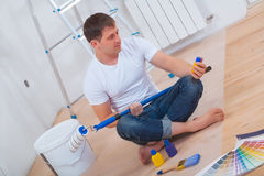 Painter sitting on floor with crossed legs and looking on bottle Royalty Free Stock Photography
