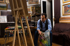 Painter sitting looking at his canvas in a gallery Stock Photo