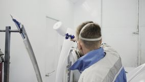 Car painter covering auto body part with primer. Painter spraying primer on the car body part before painting stock footage