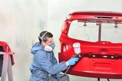 Painter spraying red base. Stock Photos