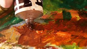 Painter squeezes brown oil paint on a palette stock footage