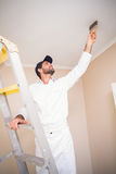 Painter standing on ladder painting roof Stock Image