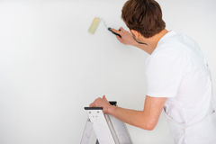 Painter standing on a stepladder Stock Photo