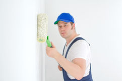 Painter in uniform paints the wall. Royalty Free Stock Photo